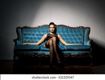 Sexy and beautiful woman in erotic lingerie and stockings posing on a blue sofa in vintage interior.