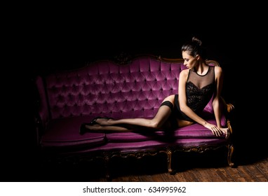 0b6b1a9e7 Sexy and beautiful woman in erotic lingerie and stockings posing on a magenta  sofa in vintage