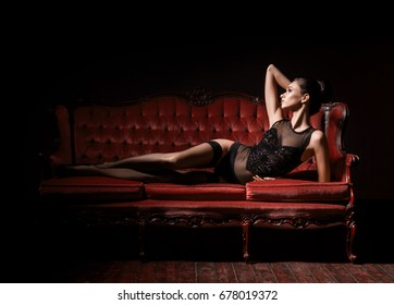 9402d6a53 Sexy and beautiful woman in erotic lingerie and stockings posing on a red  sofa in vintage
