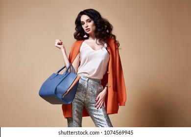 Sexy beautiful woman fashion glamour model brunette hair makeup wear pants clothes for every day casual party style accessory bag jewelry date walk girlfriend skinny body shape studio background.
