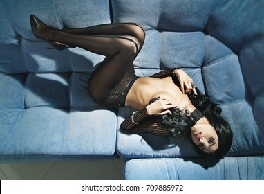 Sexy beautiful woman with long black hair and a black transparent pantyhose lying on a sofa