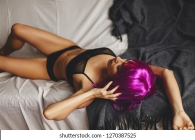 Sexy beautiful woman lying on white and grey bed in sensual black lingerie. Attractive fashion model wears pink wig with bangs. Black underwear