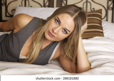Sexy. Beautiful woman lying on a bed looking at the camera