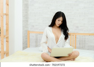 Sexy beautiful woman no bra playing notebook in white room on the bed