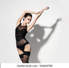 Sexy and beautiful woman in stockings and lingerie. Fashion model posing concept.