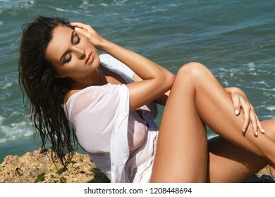 Sexy and beautiful  woman in wet tunic is posing on the beach with rocks