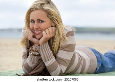 A sexy and beautiful young blond woman laying down and relaxing at the beach with golden sand and the sea behind her