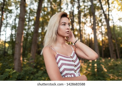Sexy beautiful young blonde woman in a vintage pink striped sundress posing on a sunny day among the trees in the park. Attractive stylish girl model resting in nature. Sunny summer day.