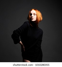 sexy Beautiful young ginger woman in black. red hair girl with make-up posing in studio