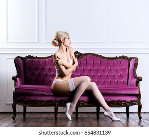 620cd0a91 Sexy and beautiful young girl in a bridal lingerie posing on a pink retro  sofa.