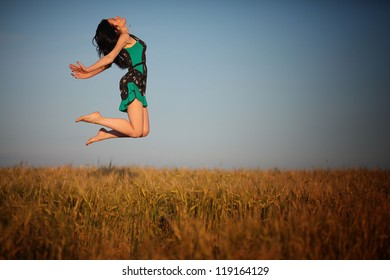 sexy beautiful young happy girl in a summer wheat field with ripe grain