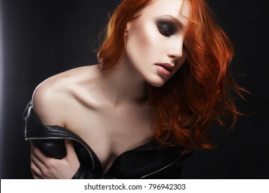 sexy Beautiful young woman in leather coat and with red hair. ginger girl with make-up fashion beauty portrait