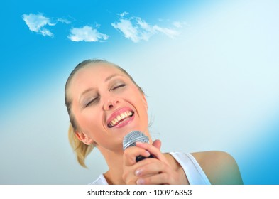 Sexy beautiful young woman singing with a microphone