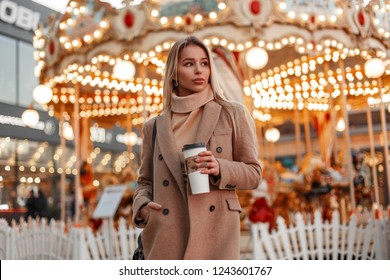 Sexy beautiful young woman in a stylish autumn coat and vintage beige knitted sweater with bag walks and drinking coffee in an amusement park in the city. Cute fashion girl
