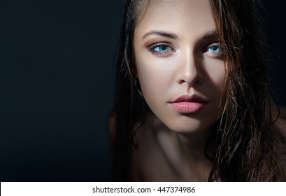 Sexy beauty. Close-up studio portrait of young fashion model with beautiful blue eyes looking at camera.