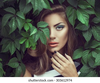 Sexy Beauty Girl with coral Lips. Provocative green Make up. Luxury Woman with Green Eyes. Fashion Brunette Portrait in wild leaves (grapes),  natural background. Gorgeous Woman Face. Long Hair