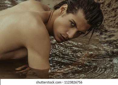 Sexy beauty male model lying stripped on the sand with nature background