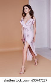 Sexy beauty woman pretty face tan skin wear pink silk dress long skinny body shape makeup cosmetic summer collection studio catalog brunette curly hair clothes for date meeting walk beach fashion bag.
