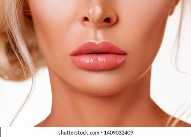 Sexy big lips. Beauty Fashion woman lips with natural Makeup. peach shine lipstick. Beauty girl face close up.