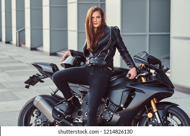 A sexy biker girl posing on her superbike outside a building.