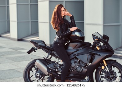 A sexy biker girl sitting on her superbike outside a building.