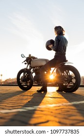 Sexy biker lady in black leather jacket and full face helmet sit on vintage custom caferacer motorbike. Urban roof parking, sunset in big city. Traveling and active hipster lifestyle. Girls power.