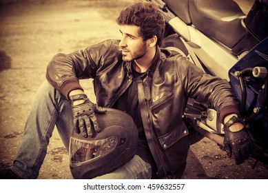 Sexy biker man wearing jeans and leather jacket sitting relaxed by his motorcycle.
