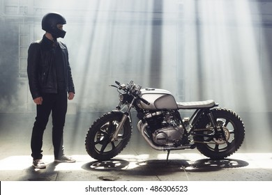Sexy biker man wearing jeans and leather jacket standing with motorcycle. Urban scene
