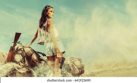 Sexy biker woman is standing near motorbike on the desert background.