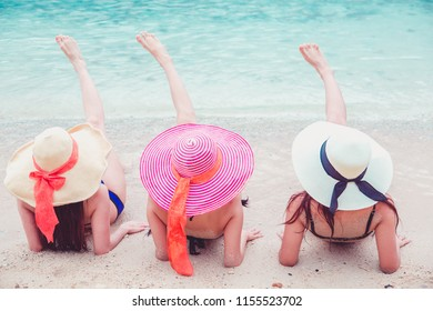 Sexy bikini body three asian women enjoy the sea by laying down on sand of beach wearing millinery hat.