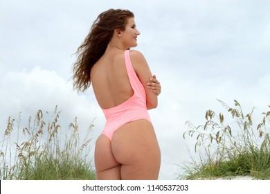 Sexy bikini girl at beach looking off camera with blue sky