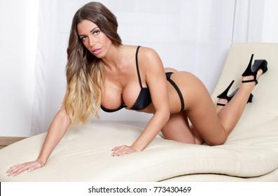 Sexy bikini lingerie fitness woman crawling on modern lounge cha