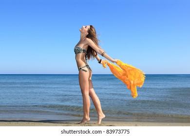 Sexy bikini model posing with a sarong on the beach in greece
