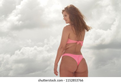 Sexy bikini woman at beach with full figure  - lens flare with clouds background