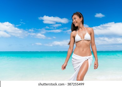 Sexy bikini woman relaxing on beach with slim stomach wearing white triangle top and pareo cover up beachwear - weight loss or epilation concept.