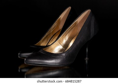 Sexy black leather woman's stiletto high heel court shoes. Moody fashion close up of quality classic design footwear with gold interior.