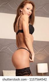Sexy black lingerie wearing woman in bedroom
