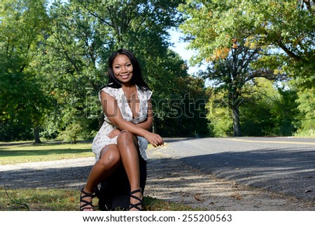6f77616546 Sexy black woman staring along country road with bag waiting for ride - wearing  short sundress