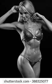 Sexy blond bodybuilder woman in  bikini on black background