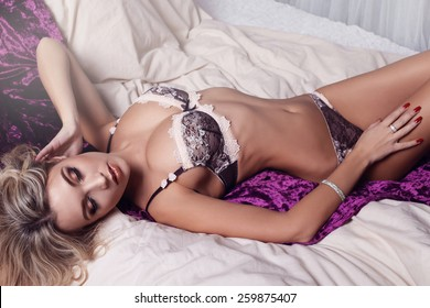 Sexy blond curly woman in lace lingerie with big breasts lying and posing on a luxurious bedspread and cushions