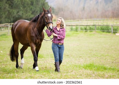Sexy blond Farm Girl leading a horse in a paddock on a farm in South Africa