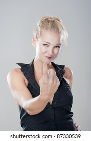 sexy blond girl showing come on gesture looking, smiling - isolated on gray