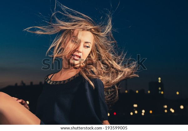 Sexy blond haired women at sunset looking at camera