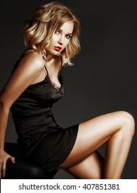 Sexy blond woman in black silk lingerie over dark background.