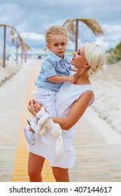 Sexy blond woman holds child on her arms.