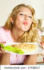 sexy blond woman at home in the kitchen eating spaghetti