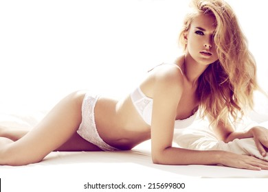 Sexy blond woman posing in white bed