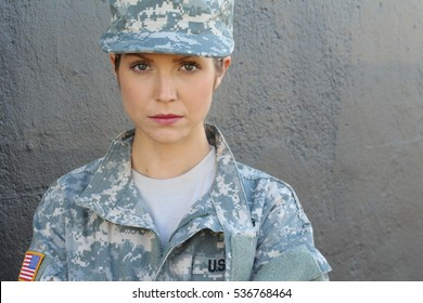 Sexy blond woman with USA flag on army uniform posing at gray wall