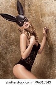 Sexy blonde beautiful woman posing in lace lingerie and black  bunny mask on gold background.