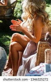 sexy blonde bridesmaid claps her hands while sitting on the highchair during the ceremony. For joy on her legs goosebumps